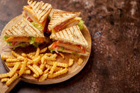 Chicken and cheese club sandwiches served on a wooden board with french fries
