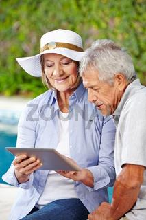 Senioren schauen auf Tablet PC im Urlaub