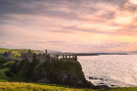 Dramatic sky over ruins of Dunluce Castle perched on the edge of cliff, Northern Ireland