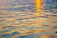 Colorful water surface with ripples at sunset