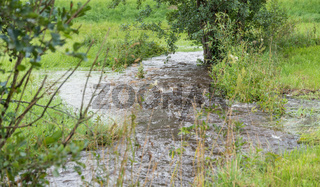 Überflutung nach einem Unwetter durch einen reißenden Bach