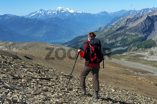 Wanderer schaut beim Aufstieg auf die Pointe de la Plaine Morte über das Rhone-Tal zum Mont Blanc Gipfel in Frankreich