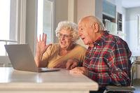 Glückliches Senioren Paar am Computer macht Videoanruf