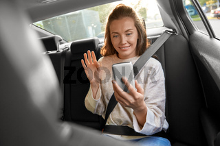 happy woman in car having video call on smartphone