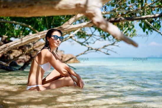 Beautiful happy woman relax in tropical beach lagoon enjoying summer vacation