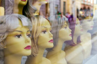 Mannequin heads wearing wigs in window of a shop display
