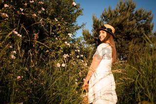 Summer portrait of young woman near wild rose bush