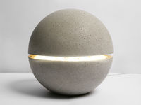 A stone lamp in the form of ball on the table.