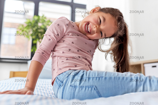 happy smiling little girl sitting on bed at home