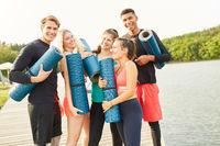 Gruppe Freunde mit Yogamatte lachen fröhlich