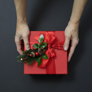 The palms are holding a red gift box with a decorative fir sprig on a black background. Top view.