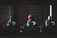 Small bronze buddhist statues with coin and knitted red hat offerings in Daisho-in temple in Miyajima, Hiroshima, Japan
