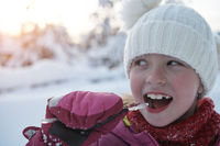 cute little girl while eating icicle on beautiful winter day