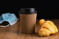 Side view of delicious croissant with take home hot coffee in paper disposable cup.