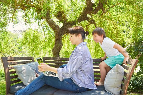 Mutter arbeitet am Laptop im Garten mit Sohn dabei