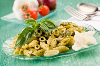 Pasta with pesto on green glass table