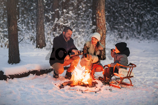 Happy family frying marshmallows over fire in winter