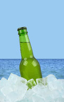 Bottle of cold lager beer on ice over sea