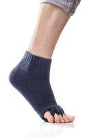 Feet with yoga toe separator socks on white background.