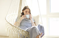 Beautiful young brunette woman drinking coffee while relaxing in knitted macrame style rocking chair