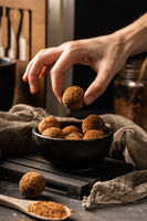 Woman hand take out a peace of homemade delicious cocoa ball with healthy ingredients from a black plate, covered with cocoa powder