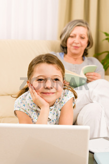 Young girl daydreaming in front of laptop