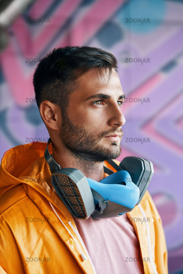 Close up portrait of handsome street artist staying on his graffiti painting background