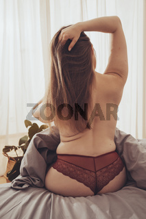 Young undressed woman sitting on bed with gray bed linen