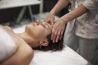 Crop massage therapist massaging face of client