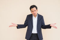 Portrait of Asian businessman wearing suit against plain background and looking angry and confused