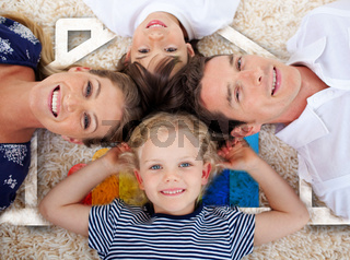 Smiling young family in front of house illustration