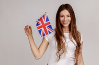 Portrait of smiling satisfied woman holding British flag, celebrating holiday, looking at camera.