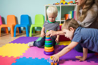 The group of kids in the kindergarten are playing with toys