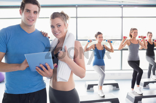 Trainer and woman smiling together during aerobics class