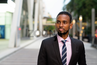 Portrait of handsome young African businessman thinking outdoors in city