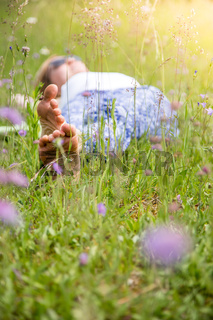 Enjoying a summer day: Young girl with yoga pants is lying in the green grass
