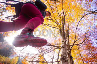 The woman hiker briskly walks in the autumn forest