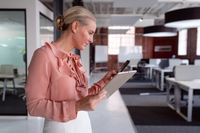 Happy caucasian businesswoman standing in office holding tablet and using smartphone