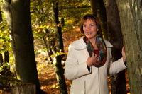 Lächelnde Frau im Herbstwald am Baum lehnend