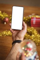 Hand holding smartphone with copy space against christmas gifts and decorations on wooden table