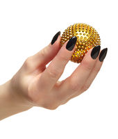 Female hand with black nails manicure and golden spiked massage ball in fingers.