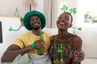 Portrait of laughing african american couple in st patrick's day costumes holding bottles of beer