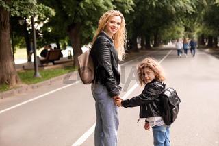 The mom and little girl walk together along the waterfront