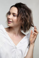 Portrait of young woman on gray background. Female posing in milky white corduroy shirt.