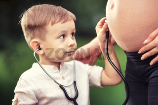 A little boy listens with interest to the stomach of a pregnant mother with a stethoscope.