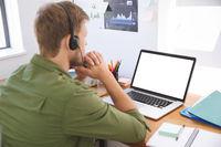 Man wearing headset using laptop at office