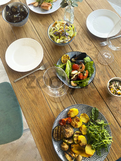 Table set for small dinner party at home or restaurant with mediterranean seafood and wine