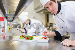 Man chef putting a strawberry in fruit salad