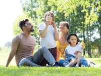 Family start soap bubble on meadow