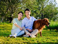 Young couple and pet dog in the park